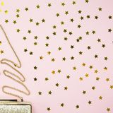 Festive evening golden clutch with star sprinkles on pink. Holid Stock Photos