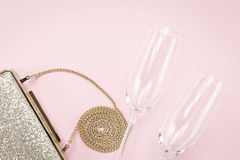 Festive evening golden clutch and two champagne glasses on pink. Holiday and celebration background. Luxury accessories and party concept. Horizontal Stock Images