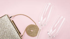 Festive evening golden clutch and two champagne glasses on pink. Holiday and celebration background. Luxury accessories and party concept. Horizontal, wide Stock Images