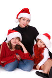 Festive family portrait. Christmas portrait of a mother with her two daughters, all of them are wearing Santa hats. White background Stock Images