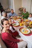Festive family smiling at camera during christmas dinner Stock Image