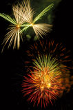 Festive fireworks. Display: white and green above multicolored bursts Stock Photos