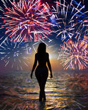 Festive fireworks over sea and silhouette woman. Festive fireworks over the sea and a silhouette of the woman going in waves Royalty Free Stock Photo