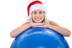 Festive fit blonde leaning on exercise ball Royalty Free Stock Photos
