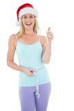 Festive fit blonde measuring her waist Royalty Free Stock Images