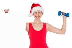 Festive fit brunette holding page and dumbbell Stock Photo
