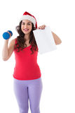 Festive fit brunette holding page and dumbbell Stock Images