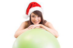 Festive fit brunette leaning on exercise ball Royalty Free Stock Images