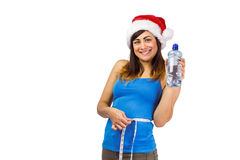 Festive fit brunette measuring her waist and holding bottle Stock Images