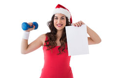 Festive fit brunette showing page and dumbbell Stock Images