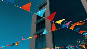 Festive flags hanging outdoors. Against blue sky and business building. 4k footage stock video footage