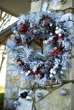 Festive flocked pine wreath. This berry and cone laden evergreen wreath is flocked to look like snow Stock Photo