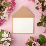 Festive flower apple tree composition and invitation on craft envelope on the pastel pink background. Overhead view.  Stock Photo