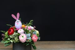 Festive flower arrangement of buttercup flowers and other plants with rabbit Easter decorated on wooden and black. Background, copy space, beautiful bouquet for Royalty Free Stock Photo