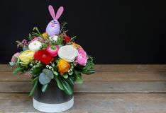 Festive flower arrangement of buttercup flowers and other plants with rabbit Easter decorated on wooden and black. Background, copy space, beautiful bouquet for Royalty Free Stock Photography