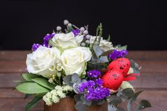 Festive flower arrangement of white roses, white and blue kermek and other plants, red eggs for Easter decorated on Royalty Free Stock Images
