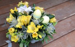 Festive flower arrangement of yellow and white freesia flowers and other plants with Easter eggs decorated on wooden. Background, beautiful bouquet for Easter Royalty Free Stock Photos