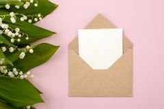 Festive flower lily of the valley composition and invitation on craft envelope on the pastel pink background. Overhead view, bouqu. Et of may lilies royalty free stock photo