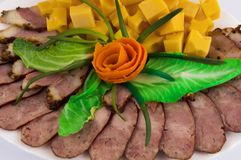 Festive food decoration. Homemade sausage, bacon, hard cheese and greens royalty free stock photography