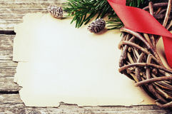 Festive frame with vintage paper and Christmas wreath. On wooden background Stock Photo