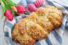 Fresh baked tasty sweet brioche for Easter with Easter eggs on a table stock photo