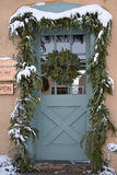 Festive Front Door Christmas. Festive front door at Christmastime. Decorated with a wreath, snow, and garland Royalty Free Stock Photography
