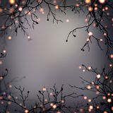 Festive garland on branches frame. Empty dark grey blurred background. Golden lights in dark night forest. Halloween party mystica. Stylish image for a variety Royalty Free Stock Photo
