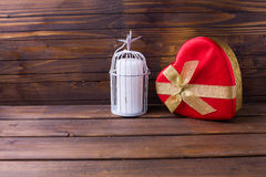 Festive gift box and candle in decorative bird cage Royalty Free Stock Photography