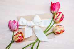 Festive gift box with fresh tulip flowers on white background Stock Image