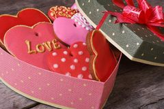 Festive gift box in heart shape with sweets on the table Stock Image