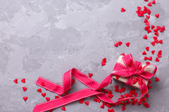 Festive gift box and many little decorative red hearts on textu royalty free stock image