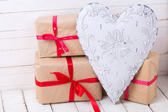 Festive gift boxes  and  big decorative heart on white wooden ba Stock Photos