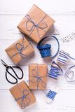 Festive gift boxes with presents, scissors,  blue ribbon  and ta. Gs on textured wooden background. Selective focus. Vertical image. Flat lay Royalty Free Stock Photography