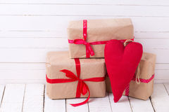 Festive gift boxes and red decorative heart  on white wooden bac Royalty Free Stock Photos