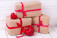 Festive gift boxes and red decorative hearts  on white wooden ba Stock Photography