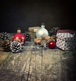 Festive Gifts with Boxes, Baubles, Pine Cones, Walnuts on Wooden Background. Royalty Free Stock Photo