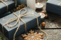Festive gifts with boxes, candle, snow, coniferous, basket, cinnamon, pine cones, nuts on wooden background. royalty free stock images