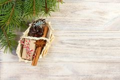 Festive Gifts with boxes, star anice, basket, cinnamon and snowflake on Wooden Background. Christmas Presents with copy space stock photography