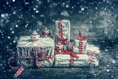 Festive gifts and presents decorating with cut paper snowflakes and red ribbons on dark rustic background. Royalty Free Stock Photo