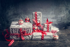Festive gifts and presents decorating with handmade cut paper snowflakes and red ribbons Stock Photos
