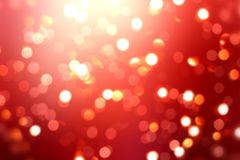 Festive glitter on red texture. Bright bokeh blurred background. New year and Christmas blank background. Stylish image for a variety of design: advertising Royalty Free Stock Photo