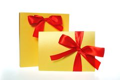 Festive gold box with a red bow Stock Photography
