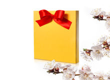 Festive gold box with a red bow on a white background Royalty Free Stock Photo