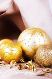 Festive gold Christmas decorations on fabric background Stock Photos