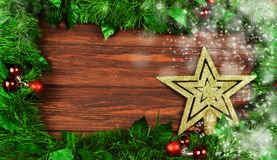 Festive gold star decoration on a Christmas tree. On a wooden background with branches of a Christmas tree and toys for the new year Stock Photography