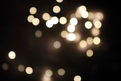 Festive golden blurred lights. Shiny bokeh. Abstract defocused lights. Glowing effect concept. Blur lights in dark night. Illuminated decoration background Royalty Free Stock Image