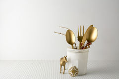 Festive golden cutlery knife and fork spoon in a white bottle,  light background Stock Photos