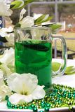 Green Beverage Closeup for St. Patrick`s Day, Beads. Festive green beads and gladiolas surrounding this mug filled with and Irish beverage.  Ideal for St Royalty Free Stock Images