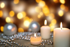 Festive greeting card with candles, pearls and christmas balls. Golden sparkling background Royalty Free Stock Image