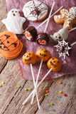 Festive Halloween cakes close-up on the table. vertical top view. Festive Halloween cake pop and gingerbread cookies close-up on the table. vertical top view Stock Photography